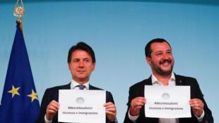 O primeiro-ministro da Itália, Giuseppe Conte, e o ministro do Interior, Matteo Salvini, seguram o nome do novo decreto escrito durante coletiva no Palácio Chigi, em Roma, Itália, em 24 de setembro de 2018.