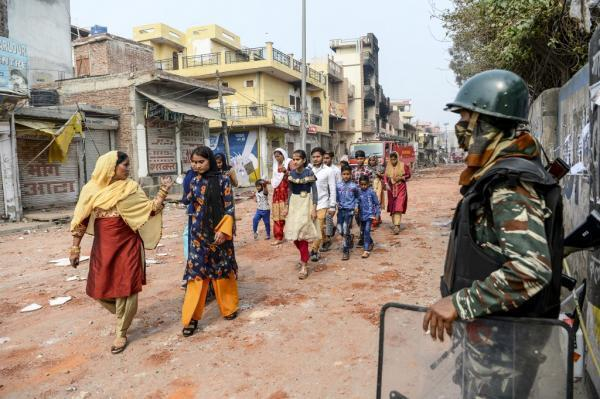 Un groupe de femmes dans une rue du nord-est de la capitale New Delhi à majorité musulmane passe devant un agent militaire, le 26 février 2020.