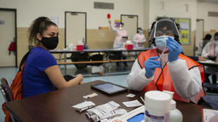 A nurse prepares a vaccine at a distribution center in the Bronx