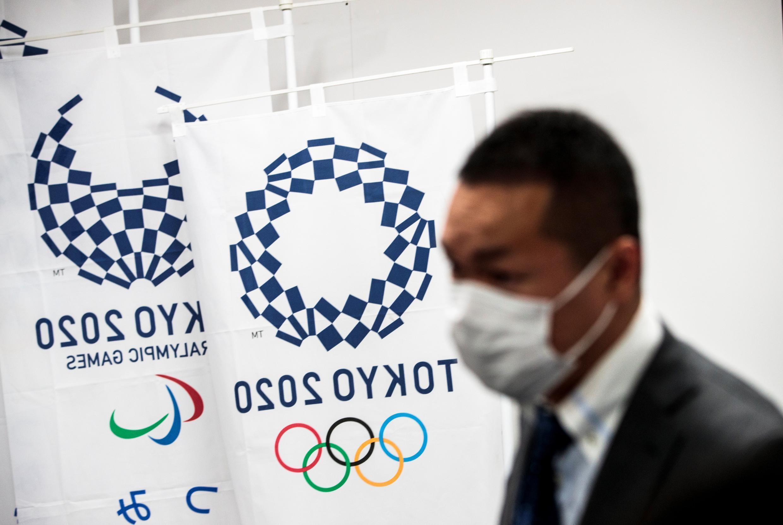 Un homme porte un masque à côté des logos des Jeux olympiques et paralympiques de Tokyo-2020 le 11 mars 2020 à Tokyo (Japon)