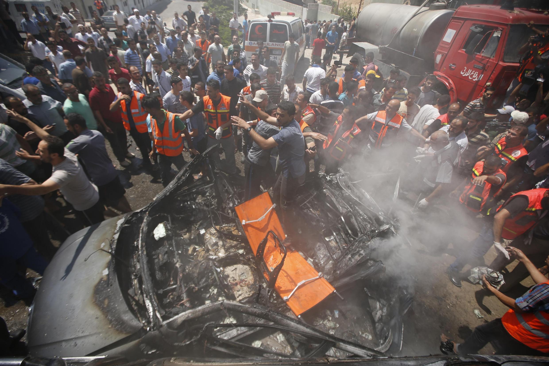 Palestinos cercam um carro atingido em Gaza por um bombardeio aéreo de Israel neste domingo, 24 de agosto.