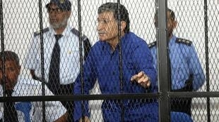 Former spy chief in Moamer Kadhafi's government, Bouzid Dorda stands behind bars in the dock during a court session in Tripoli, 5 June, 2012