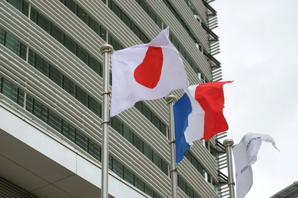 Japanese and French flags fly outside the headquarters of carmaker Nissan, a partner with France's Renault, in Yokohama, 10 December 2018.
