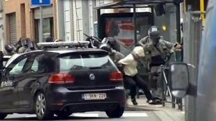 A man who appears to be Salah Abdeslam is dragged from the Brussels apartment