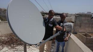 Charles-David Barry, technicien de RFI au Burkina Faso et Saliou Diao, technicien au Sénégal, vérifient les installations Ordispace de la radio Ndef Leng à Dakar.