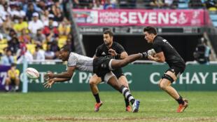 Paula Dranisinukula (izq), de Fiyi, se lanza a por el balón mientras le intenta placar el neozelandés Sam Dickson (drcha) en el torneo Rugby Sevens de Hong Kong el 6 de abril de 2019