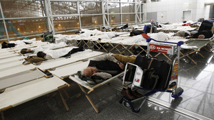 Travellers at Frankfurt airport sleep on camp beds after their flights are cancelled