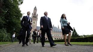 El canciller de Kosovo camina junto a miembros de su equipo en el Palacio de la Paz de la Haya.