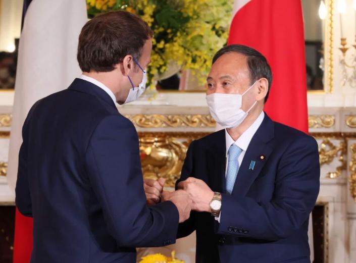 法国总统马克龙与日本首相菅义伟资料图片