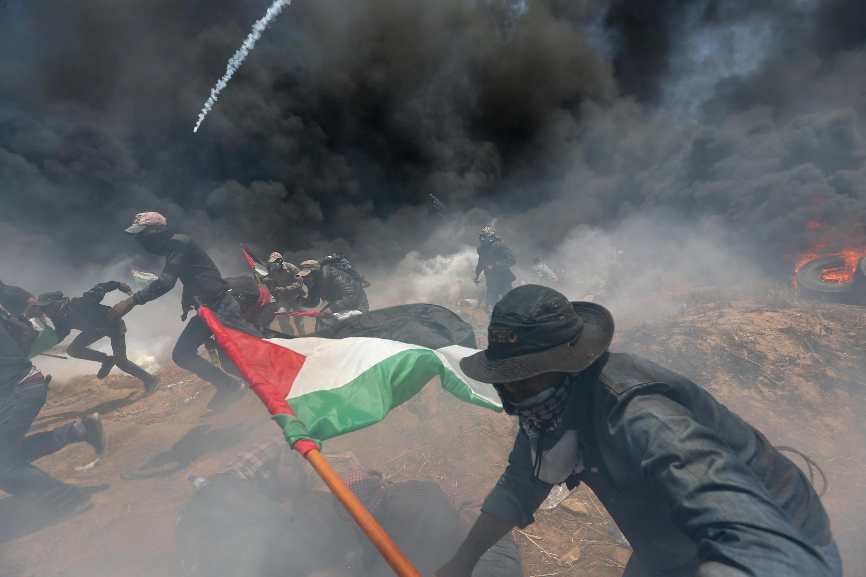 Des manifestants palestiniens au milieu des fumées et des tirs, dans la bande de Gaza, le 14 mai 2018.