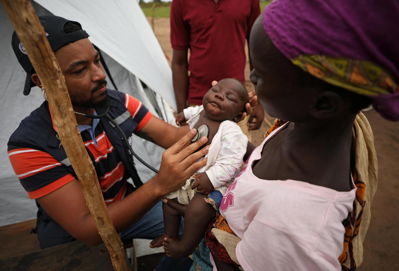 Médico examina bebê em acampamento imporvisado em Beira para receber os desabrigados em Moçambique.