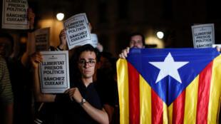 Manifestantes catalanes sostienen carteles que piden la libertad de los presos políticos