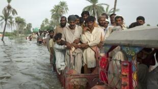 Des réfugiés juchés sur des tracteurs fuient les inondations, le 16 août 2010.