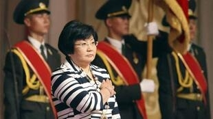 Roza Otunbayeva listens to the national anthem during her presidential swearing-in ceremony