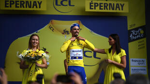 Female touch: French rider Julian Alaphilippe is helped by a hostess to put on the overall leader's yellow jersey early in last year's Tour de France
