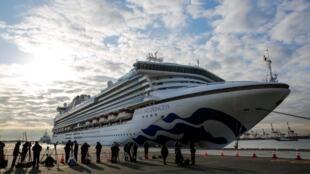 Des journalistes sont postés à côté du bateau de croisière «Diamond Princess», ancré au terminal de Daikoku à Yokohama, le 7 février 2020.