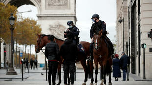 Mounted police officers check Covid lockdown exemption certificates in central Paris.