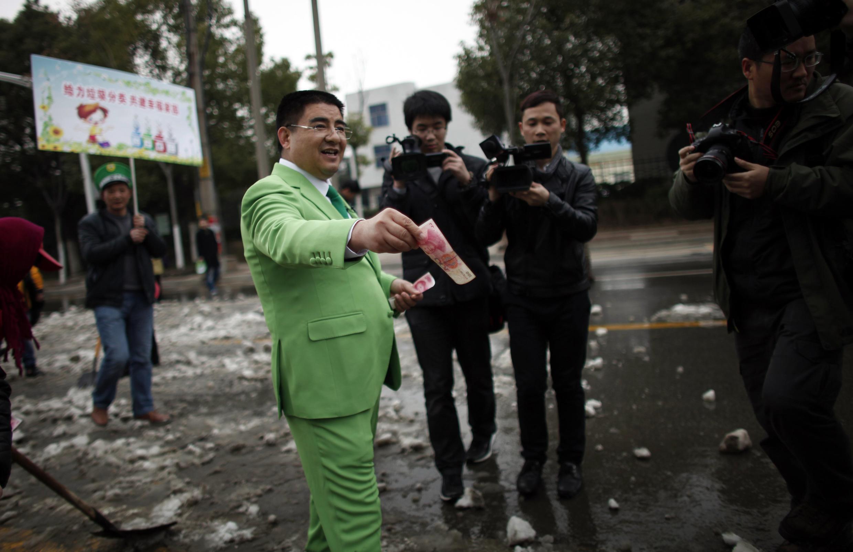Chen Guangbiao donne de l'argent aux éboueurs à Nanjing en février 2013.