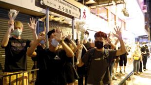"""2020年8月31日,香港亲民主派支持者在太子站集会纪念反修例运动中8-31暴力事件一周年,并举手重申运动诉求:""""五大诉求,缺一不可""""。"""