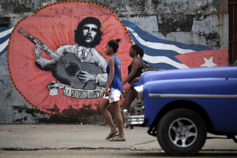 Mujeres caminan delante de un mural que representa al Che Guevara, La Habana, Cuba, 19 de marzo de  2016.