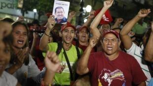 Des partisans de Nicolas Maduro brandissant le portrait d'Hugo Chavez à Caracas, le 16 avril 2013.