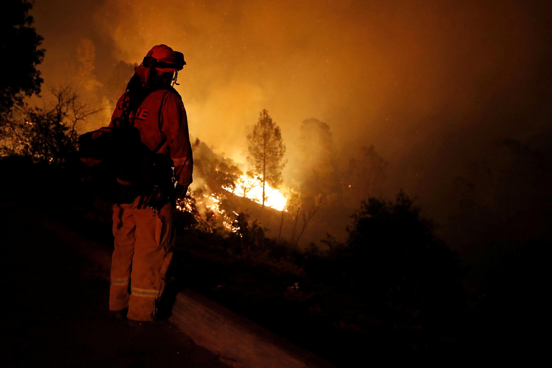 Un bombero observa impotente el avance de Carr fire hacia una colina.