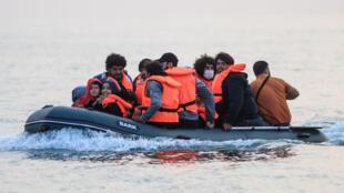 El migrante kuwaití Walid (dcha) cruza el Canal de la Mancha rumbo a Inglaterra junto a otros migrantes en una embarcación hinchable que zarpó del norte de Francia, el 11 de septiembre de 2020