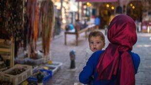 Femme portant son bébé dans la rue à Antalya (Turquie) le 25 août 2017.