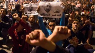 Des manifestants brandissent une image de Nasser Zafzafi, leader du mouvement de protestation dans le Rif marocain, lors d'un défilé à Al Hoceïma le 29 mai 2017.