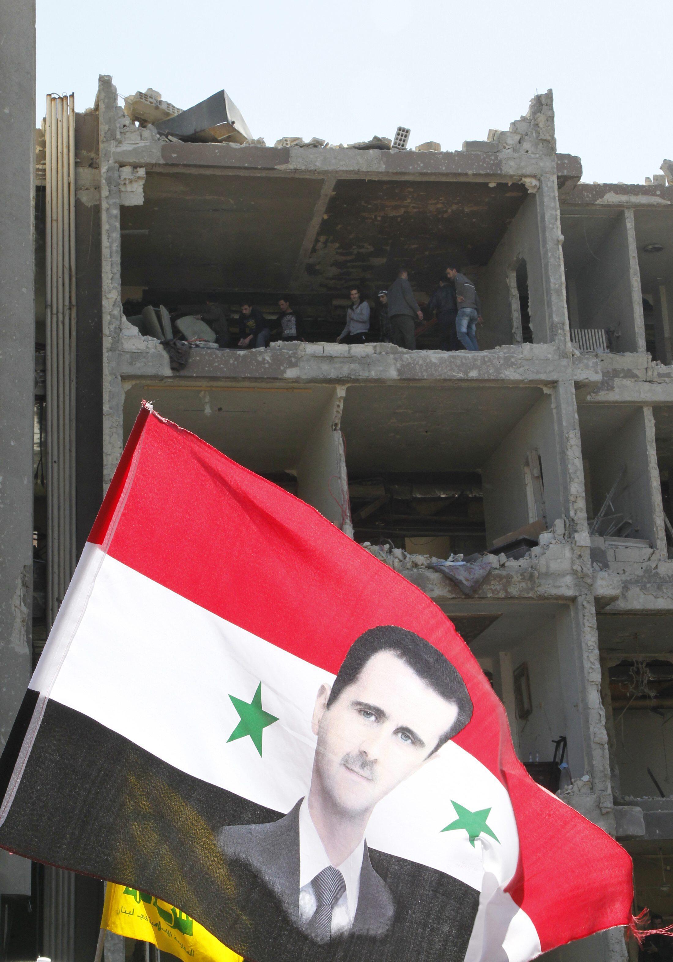 Bandeira síria com a imagem do presidente Bashar al-Assad diante de um prédio após as explosões em um bairro de Damasco.