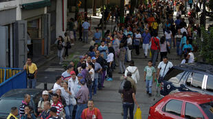 Filas em Caracas para entregar as notas de 100 bolívares nos bancos da Venezuela.