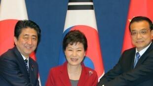 La présidente coréenne Park Geun-hye (C), entourée par le Premier ministre chinois Li Keqiang (D) et par le Premier ministre japonais Shinzo Abe (G), lors d'un sommet trilatéral à Séoul, le 1er novembre 2015.