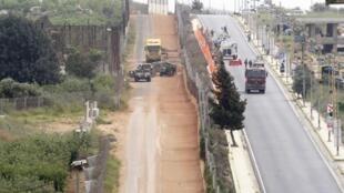 Soldados da Finul patrulham construção do muro israelense na fronteira com a cidade libanesa de Kfar Kila.