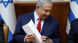 O premiê Benjamin Netanyahu aguarda o início de uma reunião ministerial em seu gabinete, neste domingo (12), em Jerusalém.