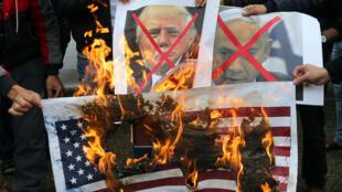 Queima de bandeiras americanas e  de cartazes com a figura do Presidente Donald Trump  e do Primeiro-ministro  Benyamin Netanyahu em Rafah(Gaza) no dia 6  de Dezembro  de  2017  . REUTERS/Ibraheem Abu Mustafa