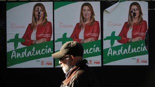 A man walks past ripped posters of Andalusian Regional President and candidate Susana Diaz for the Andalusian regional elections in Ronda, Spain