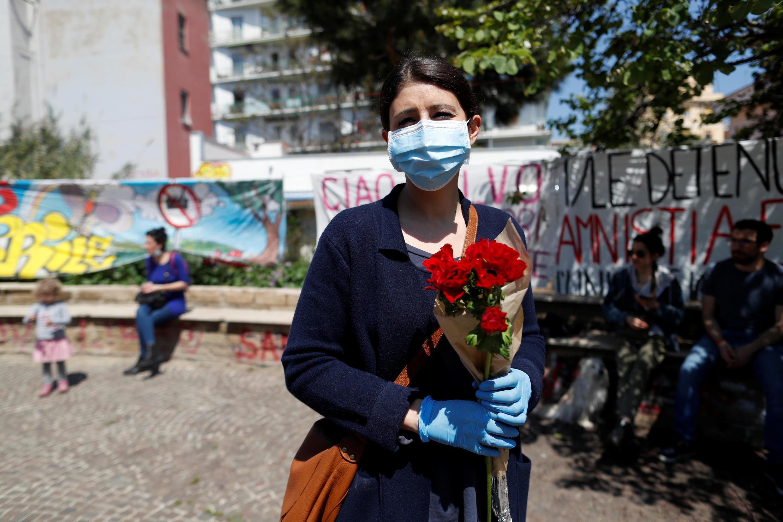 Một người phụ nữ Ý đeo khẩu trang cầm bó hoa mừng ngày Giải Phóng. Ảnh chụp tại Roma, ngày 25/04/2020.