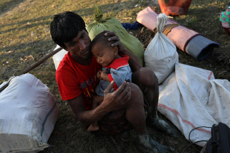 Hai cha con người Rohingya ngồi nghỉ sau khi vượt sông Naf trên một chiếc bè tạm bợ để đến Bangladesh tị nạn. Teknaf, ngày 27/11/2017.