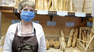A baker wears a protective face mask distributed by the city hall and made in Cannes as she poses in her bakery in Cannes, as the spread of the coronavirus disease continues in France, April 8, 2020.