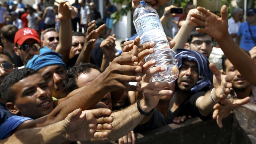 Migrantes na ilha de Kos, na Grécia, recebem água em campo improvisado