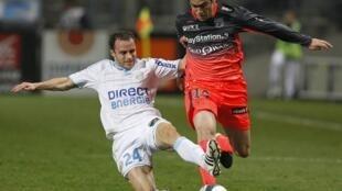 Một pha tranh bóng giữa cầu thủ đội Olympique Lyon (áo trắng) và Olympique Marseilles (áo đỏ).