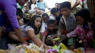 Des déplacés de l'Etat Shan qui ont fui les combats  entre l'armée gouvernementale et  trois groupes rebelles prennent de la nourriture mise à leur disposition dans un centre d'hébergement temporaire. Photo datée du 17 novembre 2015.