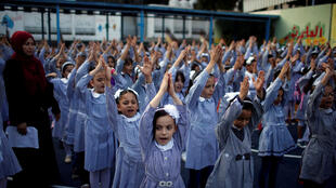 Palestinian schoolgirls do morning exercises at an Unrwa-run school on Thursday, the first day of a new school year, in Gaza City