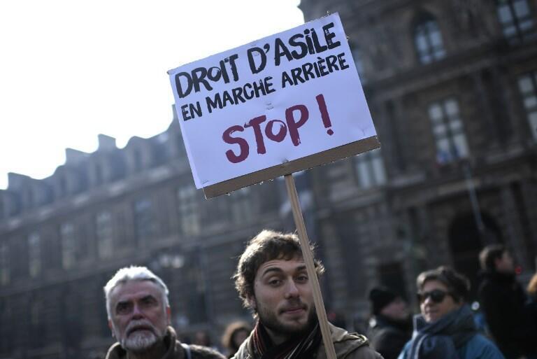Un jeune homme manifeste devant l'Office français des réfugiés et des apatrides (Ofpra), pour protester contre la loi sur l'immigration, le 21 février 2018 à Paris. La loi sera adoptée en août 2018.