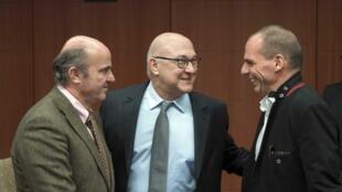 O ministro das Finanças grego, Yanis Varoufakis, à direita, com homólogos francês, Michel Sapin, no centro, e o espanhol, Luis de Guindos, à esquerda da foto, a 20 de 20 fevereiro em Bruxelas.