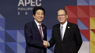 Japan's Prime Minister Shinzo Abe (L) is greeted by Filipino President Benigno Aquino III as he arrives for the Asia-Pacific Economic Cooperation (APEC) leaders meeting in Manila, Philippines, November 19, 2015.