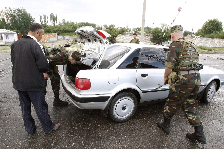 Милиционеры проверяют автомобиль в Оше.