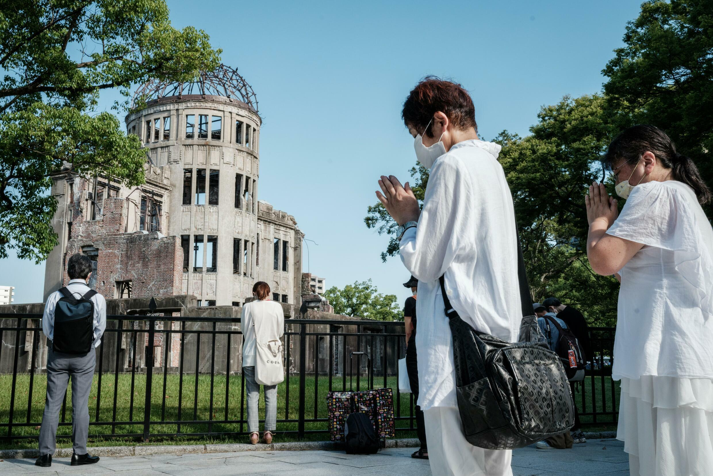 People offer prayers by the Atomic Bomb Dome in Hiroshima