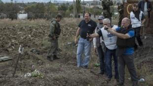 Представители ОБСЕ фотографируют место, где, по данным сепаратистов,  были захоронены мирные жители, 23 сентября 2014 г.