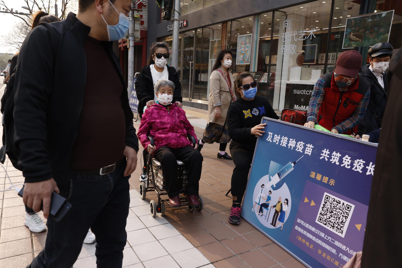 4月9日的北京街頭,一名女子被推着經過一個疫苗宣傳站